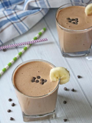 two chocolate milk shakes i short cups toppediwth chocolate chips and a banana on the rim