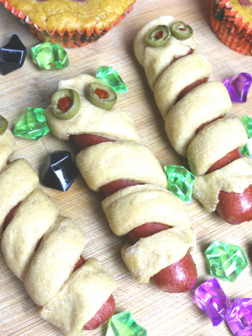hot dogs wrapped in bread strips to look like mummy dogs with green olives as eyes