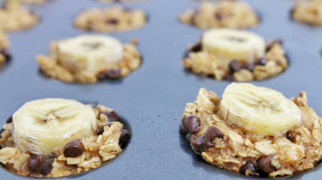 pan of oatmeal muffins each topped with a banana slice and chocolate chips