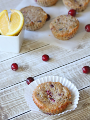 top view of muffins in a muffin cup surrounded by cranberries
