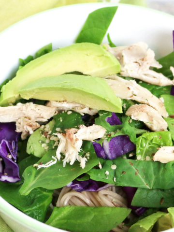 a bowl with brown yakisoba noodles, lettuce, purple cabbage, avocados and shredded chicken