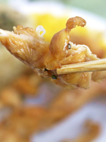 a bite sized piece of chicken being held up with chopsticks