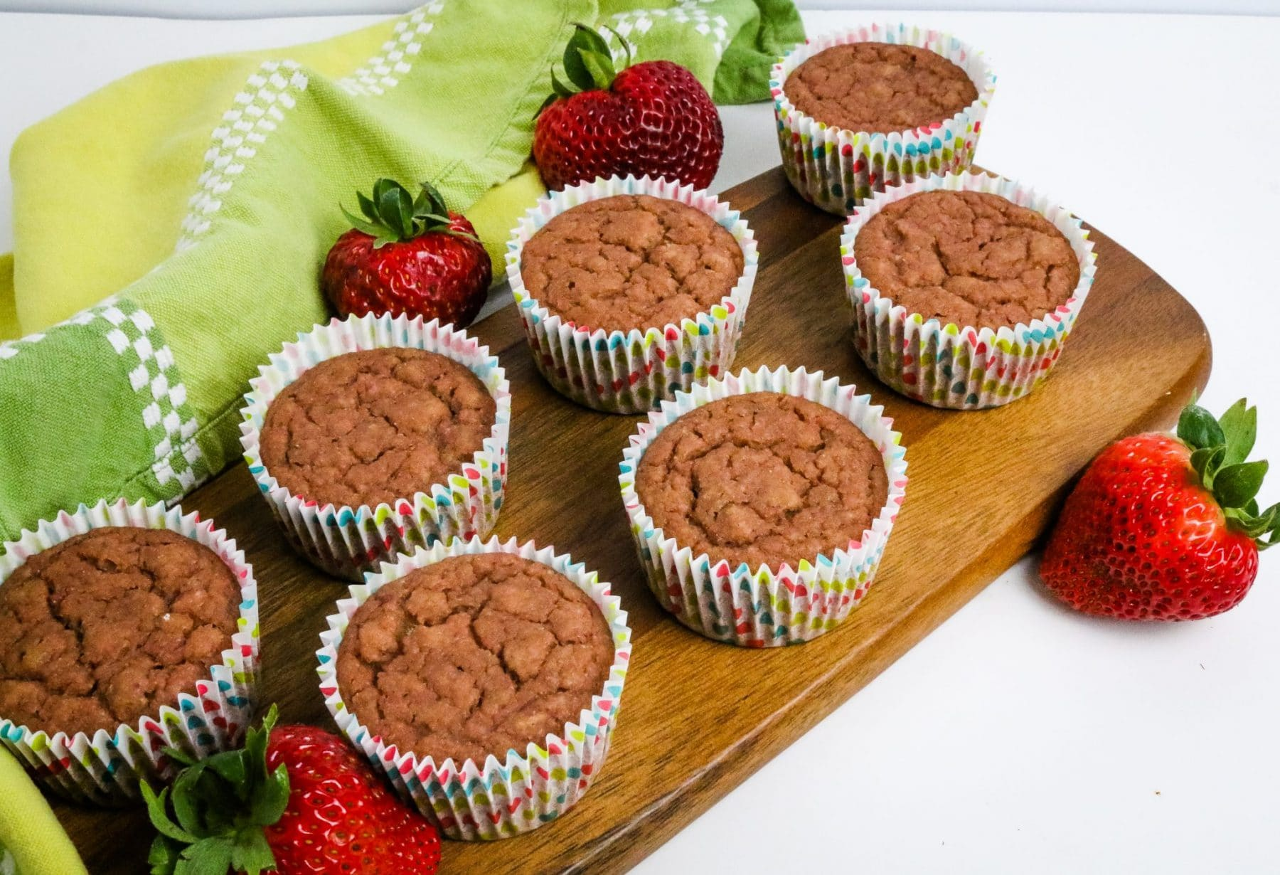 strawberry muffins on a brown cutting board