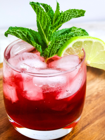red pomegranate in a glass with a mint leaf