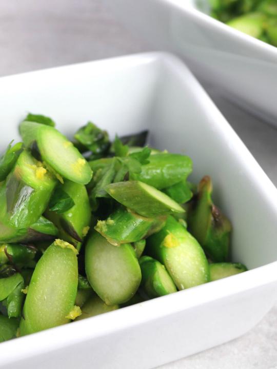 chopped asparagus in a quare white bowl