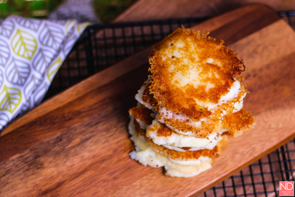 potato cakes stacked on a cutting board