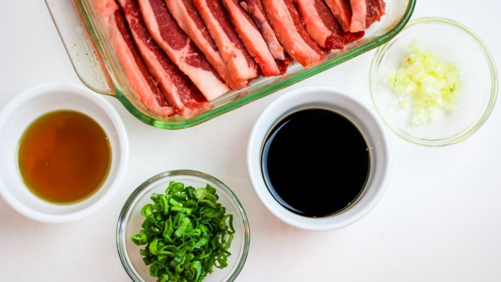 top view of the ingredients - raw spareribs, soy sauce, green onions, sesame oil and garlic