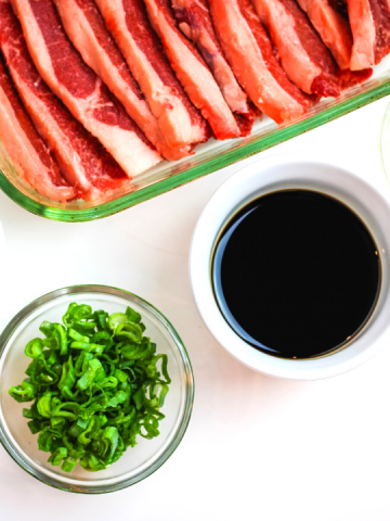 a glass pan of short ribs, a round bowl of soy sauce and green onions