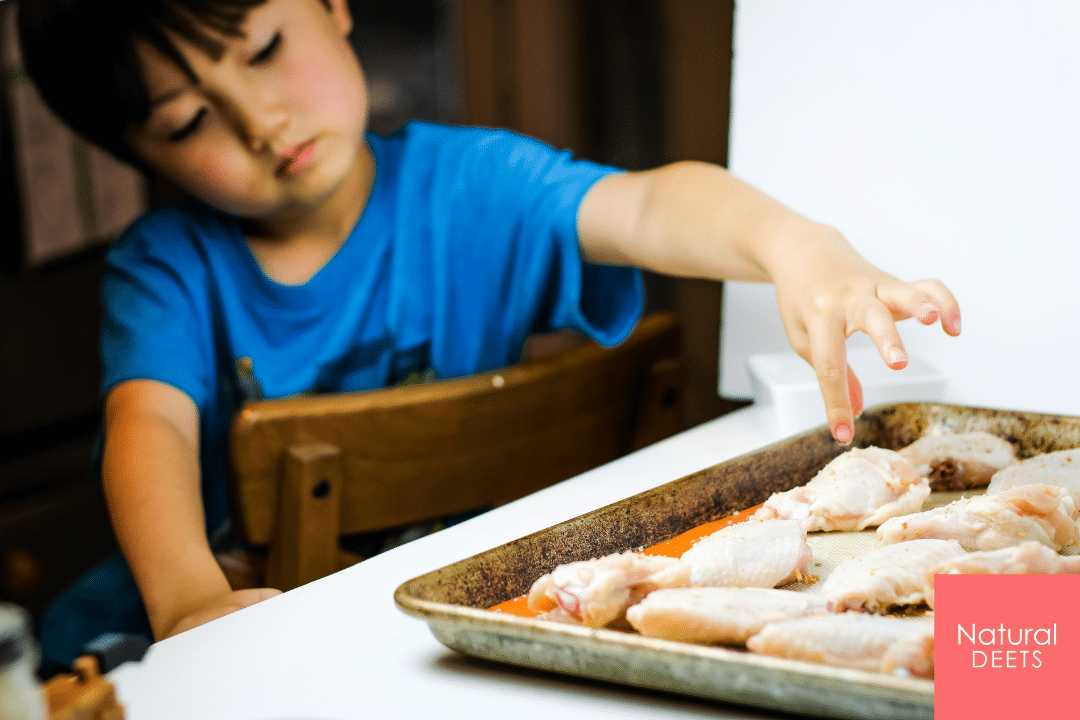 picture of my son sprinkling seasoning on the chicken wings