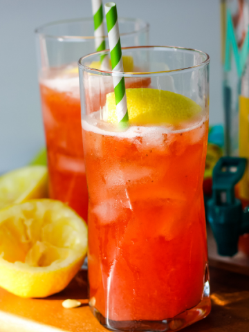 two glasses of bright pink strawberry lemondade with green straws and lemons