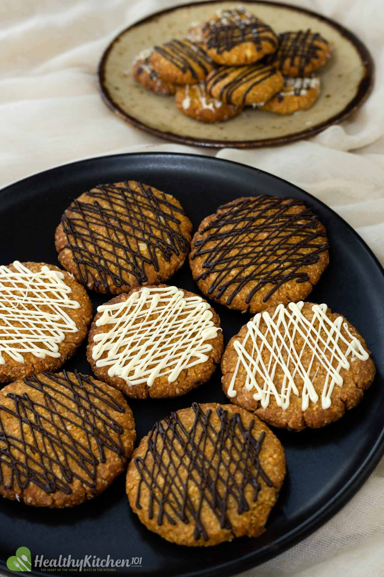 a black plate with round pumpkin cookies on it. Some cookies have a white drizzle and some have brown drizzle