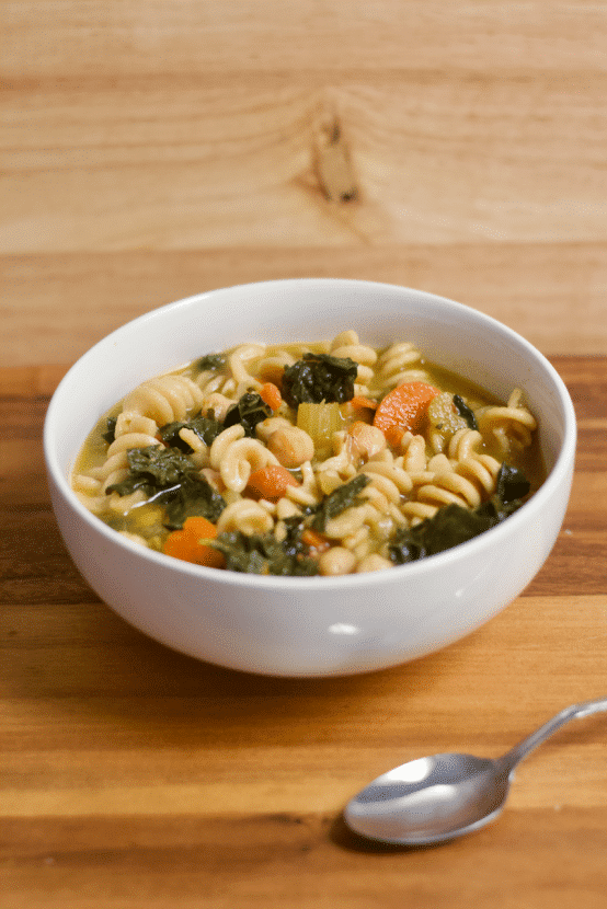 A picture of a vegan chickpea noodle soup in a bowl on a wood surface