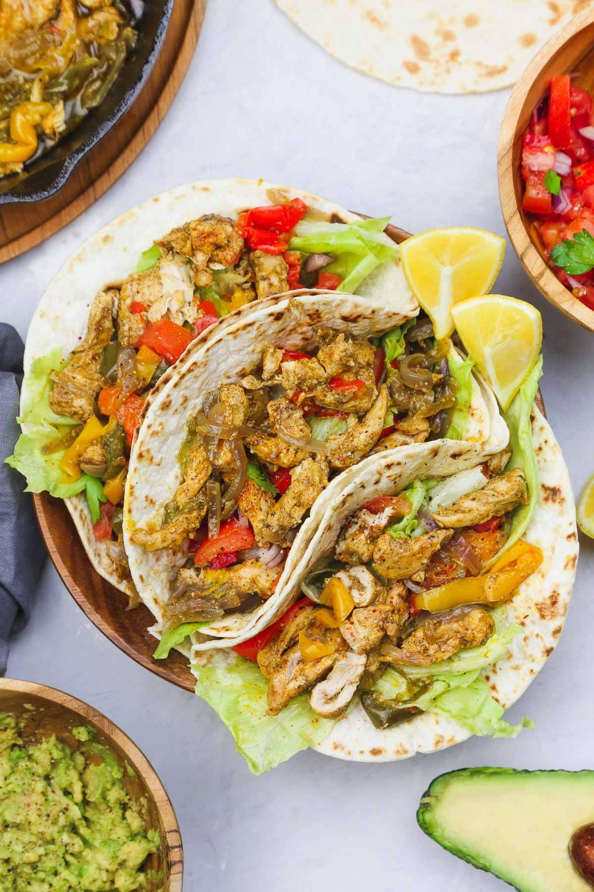 a picture of fajitas on a table with vegetables