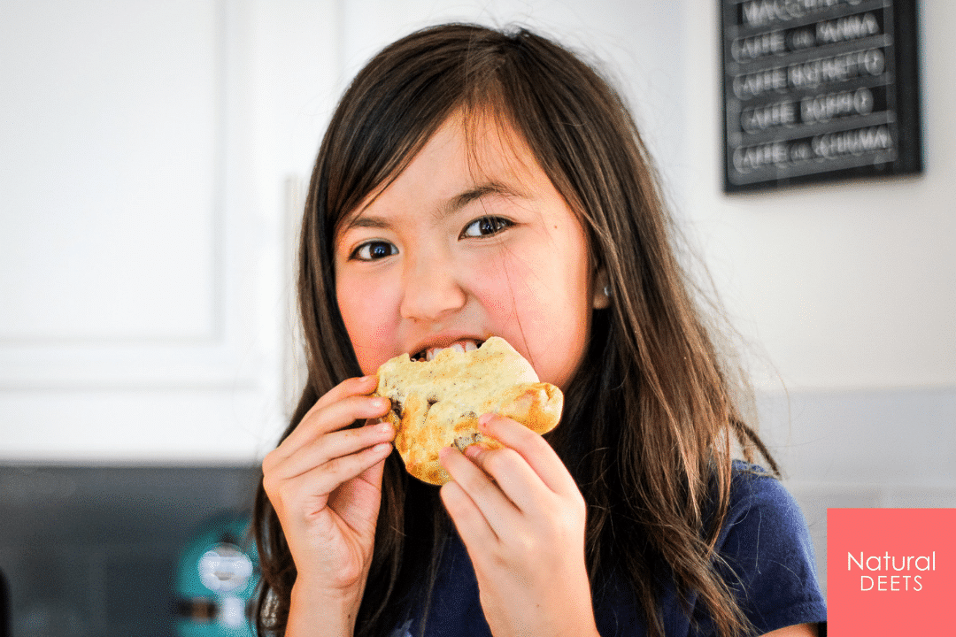 A picture of a girl eating a calzone and smiling