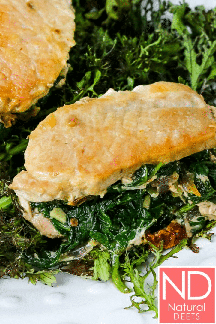 a picture of pork chops stuffed with spinach on a plate of mustard greens