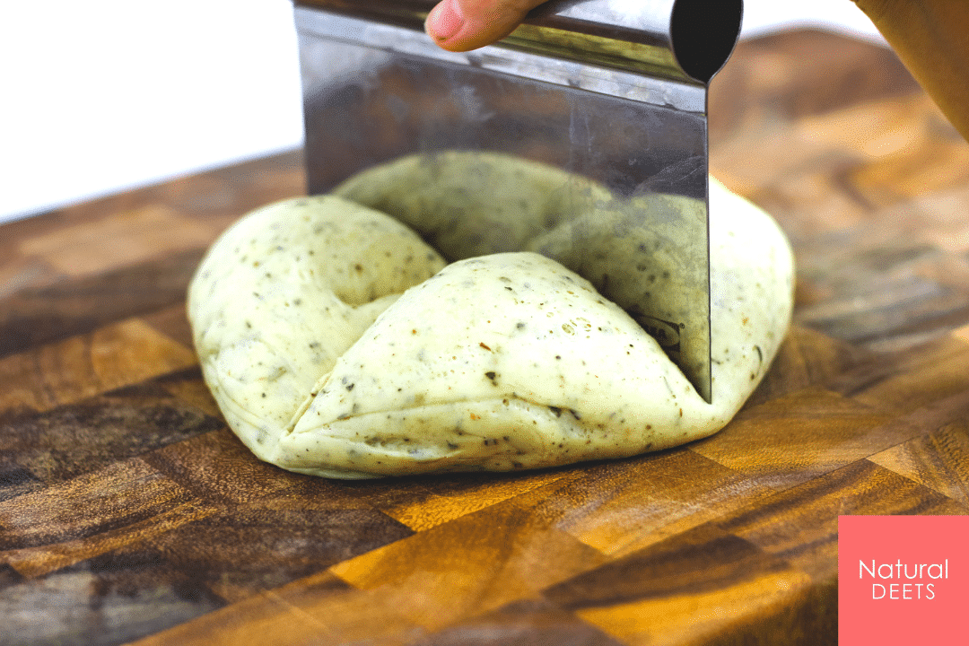 picture of a pastry cutter cutting pizza dough into 4 pieces