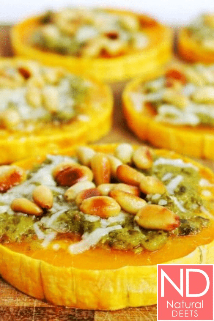 a picture of a cutting board placed on teh diagonal with bitternut squash rounds topped with pesto, parmesan and pine nuts