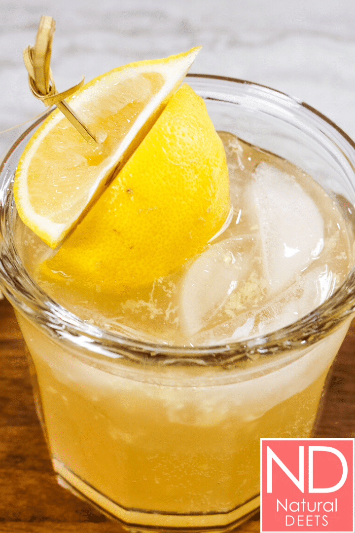 a vertical picture of a cup with ice, lemon wedges and filled with yellow colored kombucha