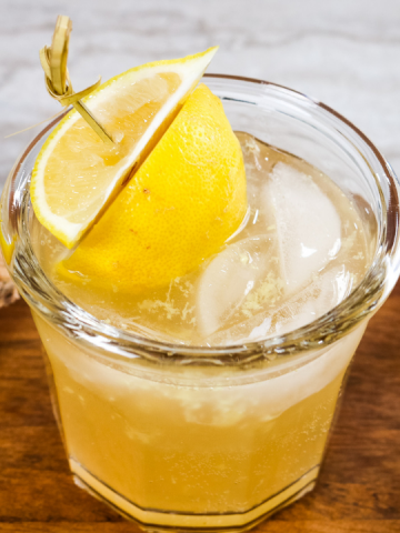 low glass with yellow kombucha, ice and a lemon on a toothpick