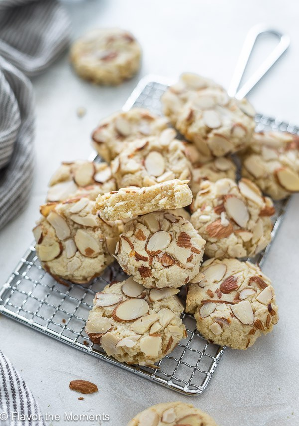 A pile of greek almond cookies whick are white in color and covered in slivered almonds