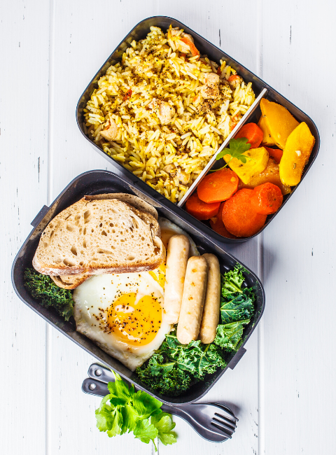 top view of two containers filled with food. One with kale, bread and a hard boiled egg and one rice and cooked carrots