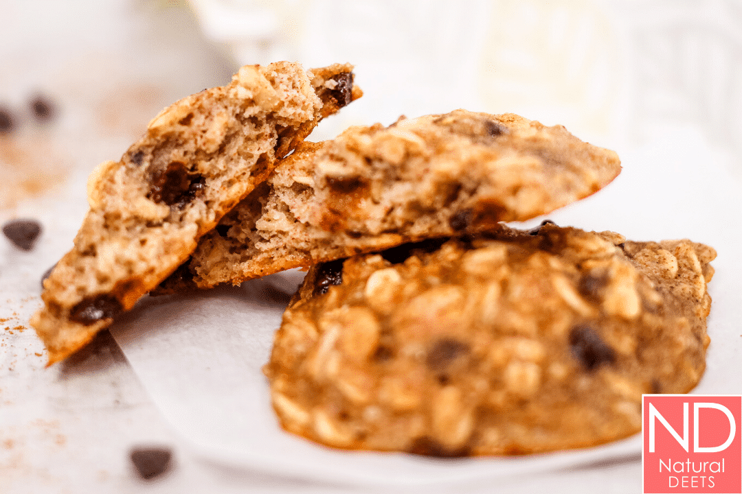 a picture of an oatmeal cookie broken in half and placed on a whole cookies so you can see the chewy middles