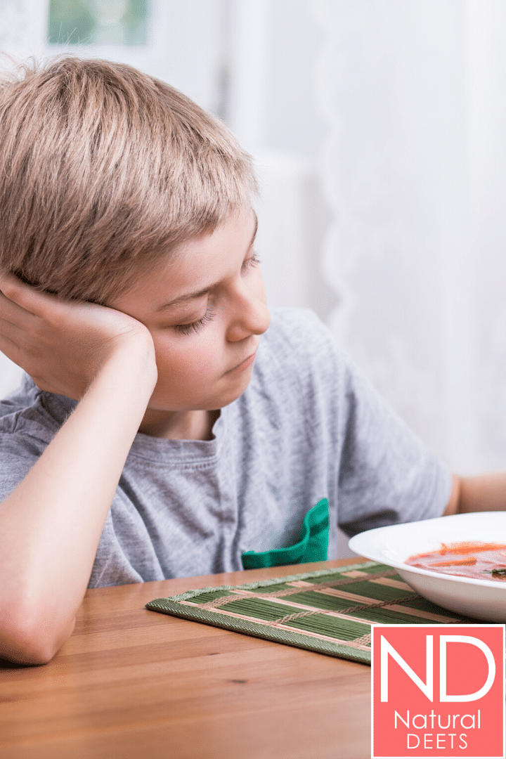 a picture of a kid resting is head on his hand in front of a bowl of soup