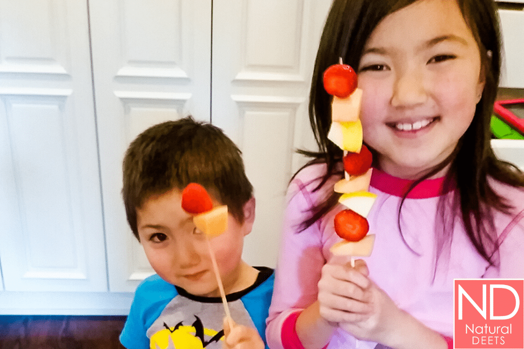 a picture of 2 kids holding skewers with fruit pieces on it