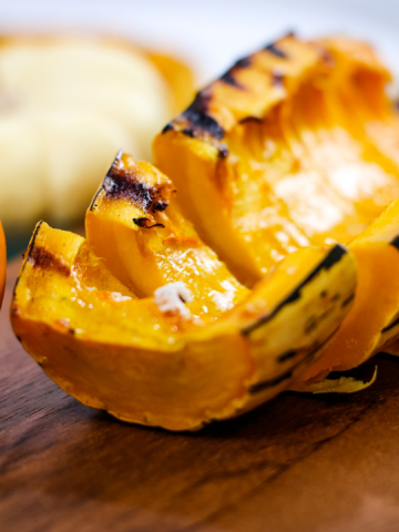 half of a delicata squash sliced and placed on a cutting board