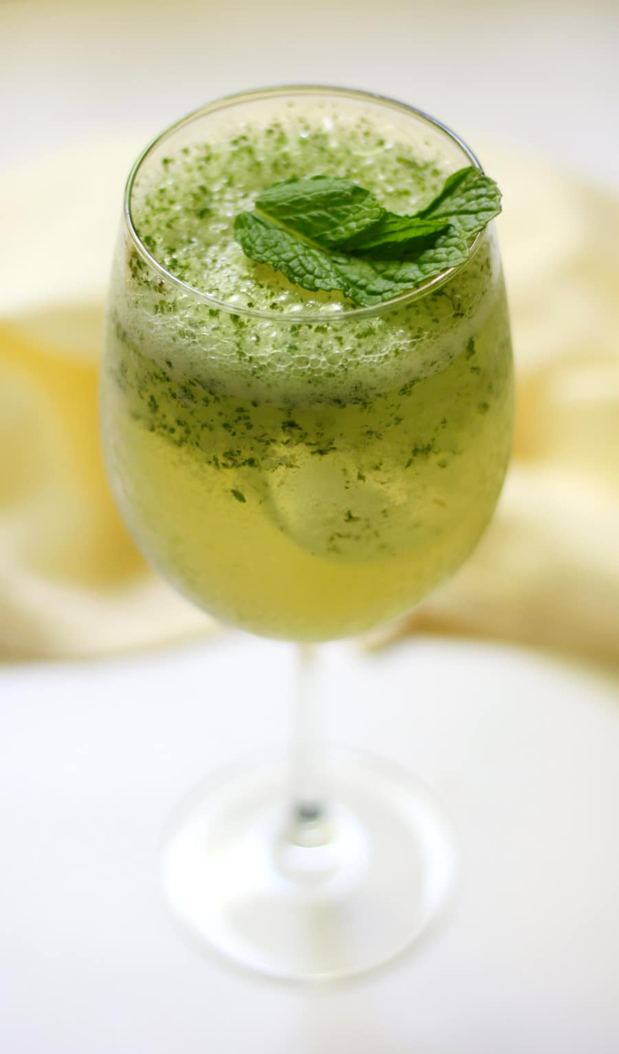 a glass with green tea and garnished with green tea flakes and mint