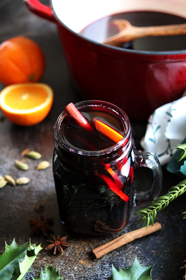a mason jar with dark red gluhwein in a mug with cinnamon sticks and orange slices