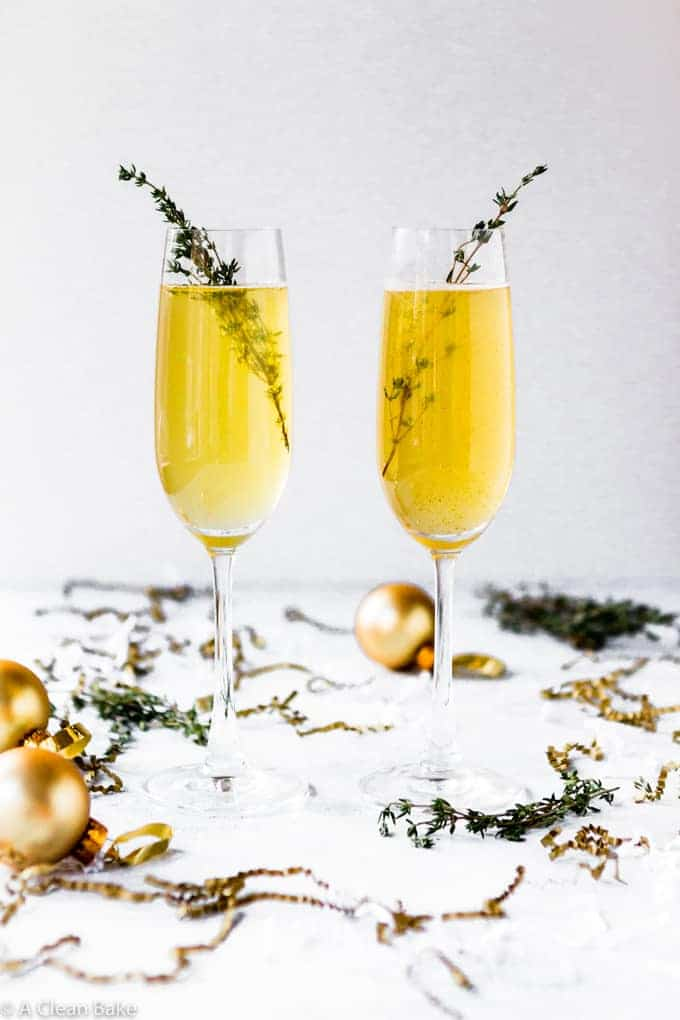 picture of 2 champagne glasses with gold colored champagne and thyme leaves as garinsh