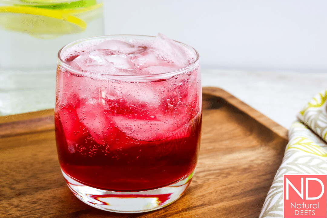 glass with pomegranate juice and ice on a brown wooden platter