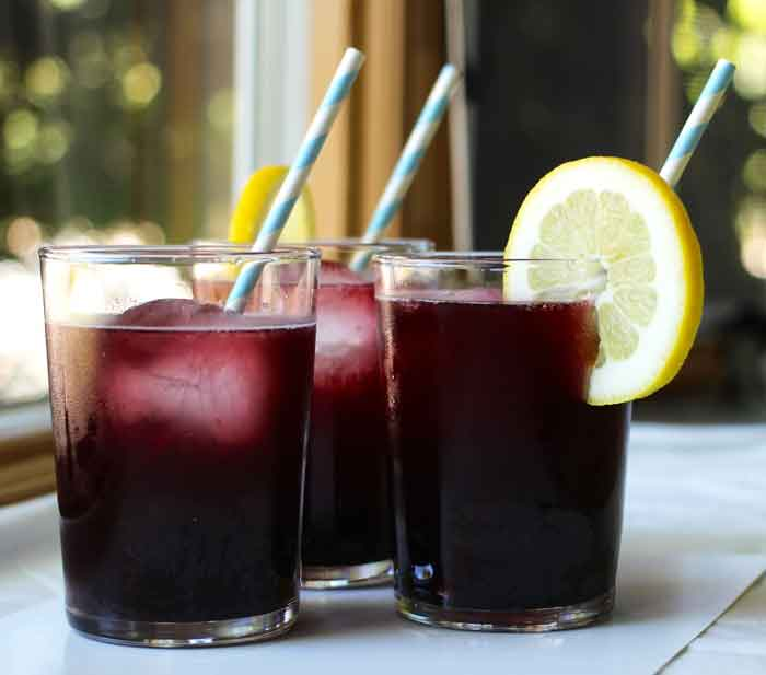 a dark purple drink in a glass garnished with a straw and lemon