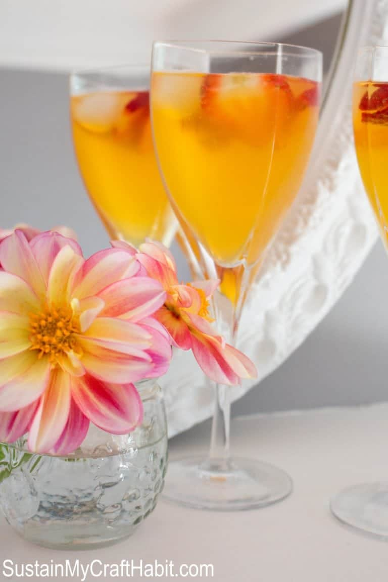 orange colored peach bellini in a glass with strawberries as garnish
