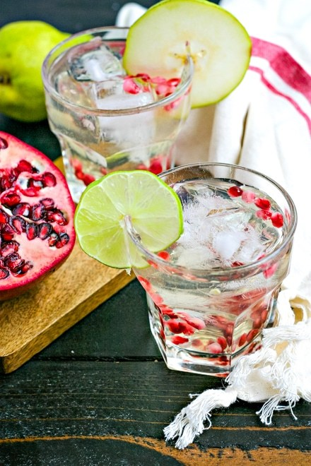 glass with white liquor and sprinkled with pomegranate seeds and garnished with a lime round