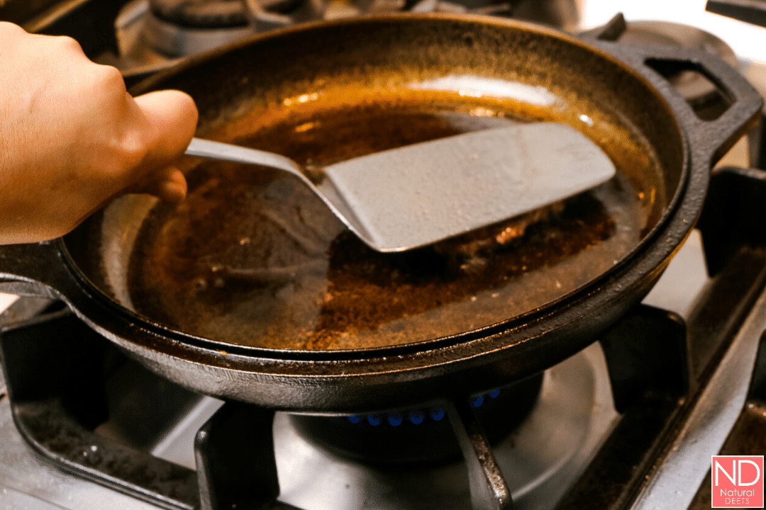 a picture of a spatula smashing a hamburger patty in a cast iron skillet