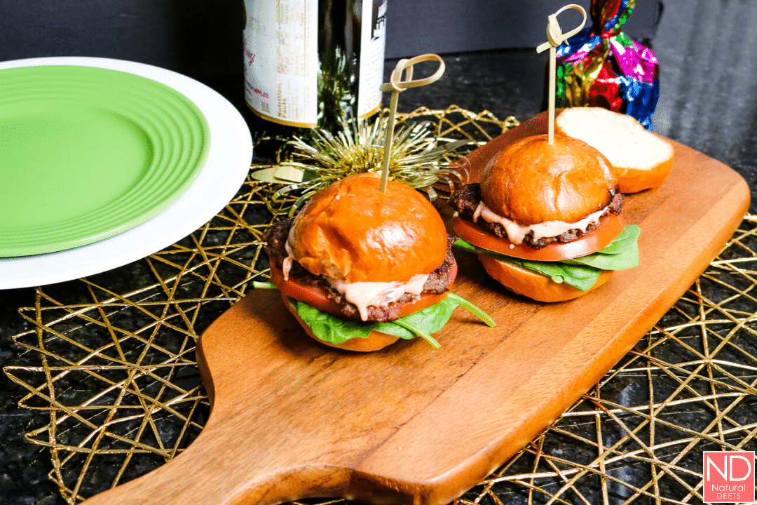 picture of two burger sliders on a wooden cutting board