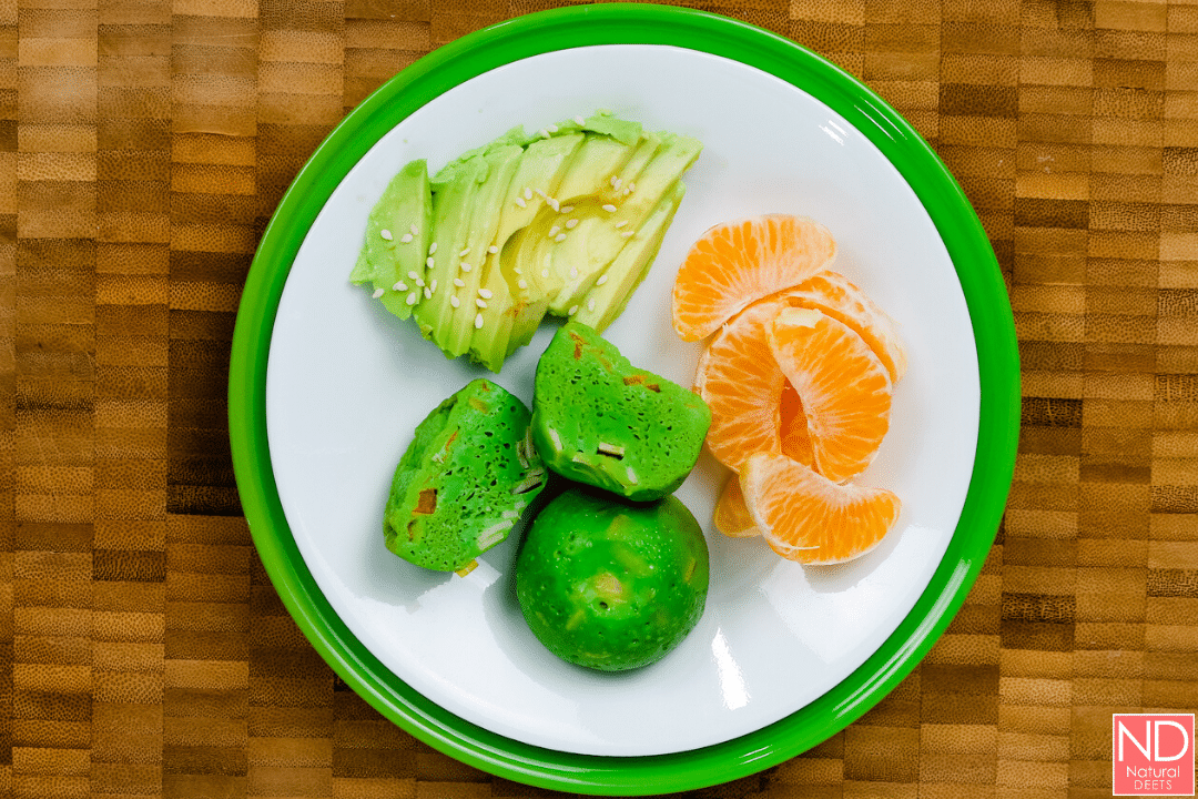 a top down picture of the green egg bites on a plate with oranges and avocado slices