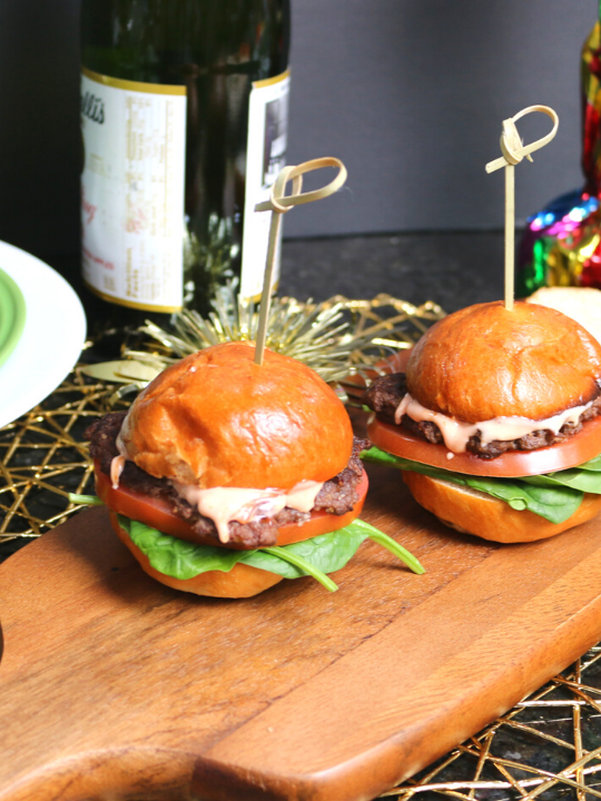 two sliders on a wooden cutting board