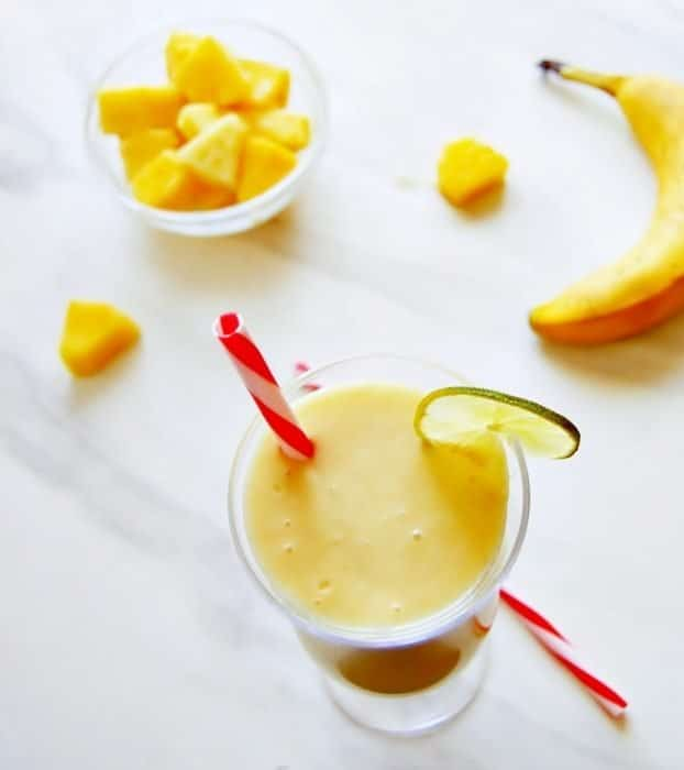 a top view of on orange smoothie with a red straw garnished with frozen mangoes