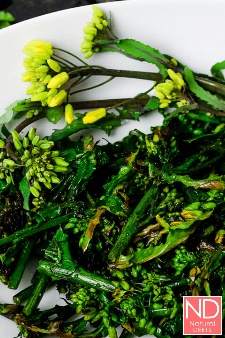 picture of green broccolini with yellow flowers contrasting with a white plate