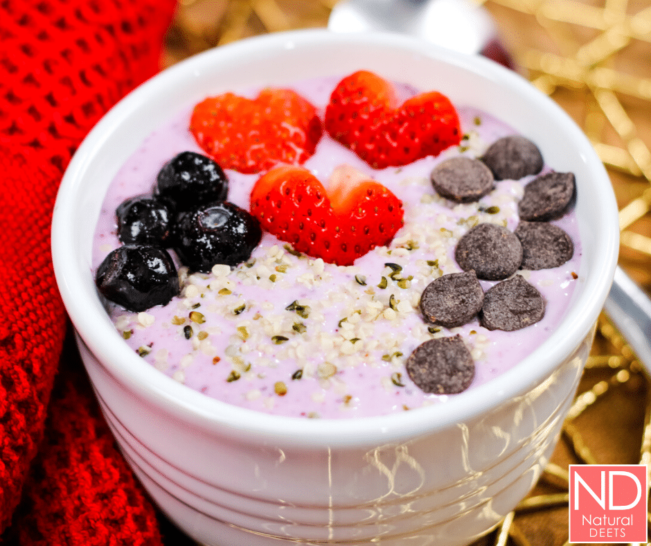 picture of blueberry smoothie bowl in a white bowl topped with hemp hearts, blueberries and strawberries