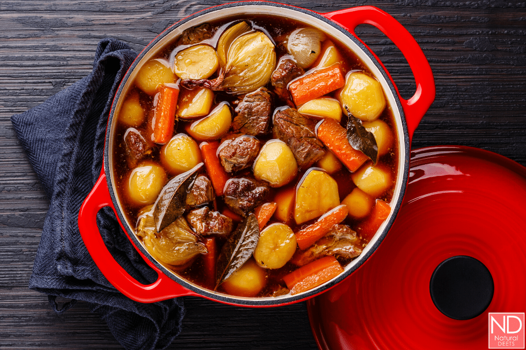 a top down picture of a red enameled cast iron pot with beef stew
