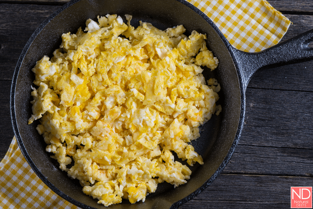 scrambled eggs in a cast iron skillet on a white and yellow checkered napkin