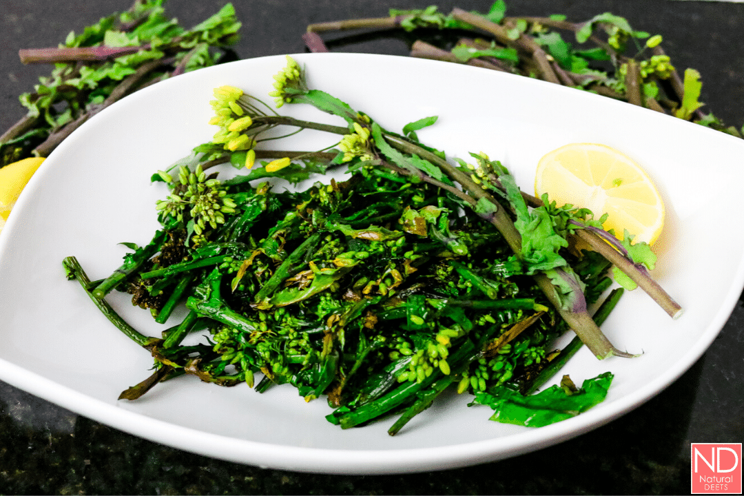 a horizontal picture of a white oblong plate iwth broccolini on it on top of a black countertop