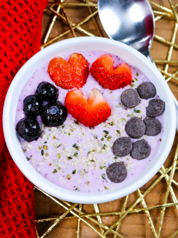 white bowl with purple colored yogurt topped with blueberries, strawberries cut into hearts, chocolate chips and hemp seeds