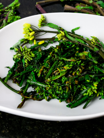 broccolini with yellow flowers in a white bowl garnished with a lemon