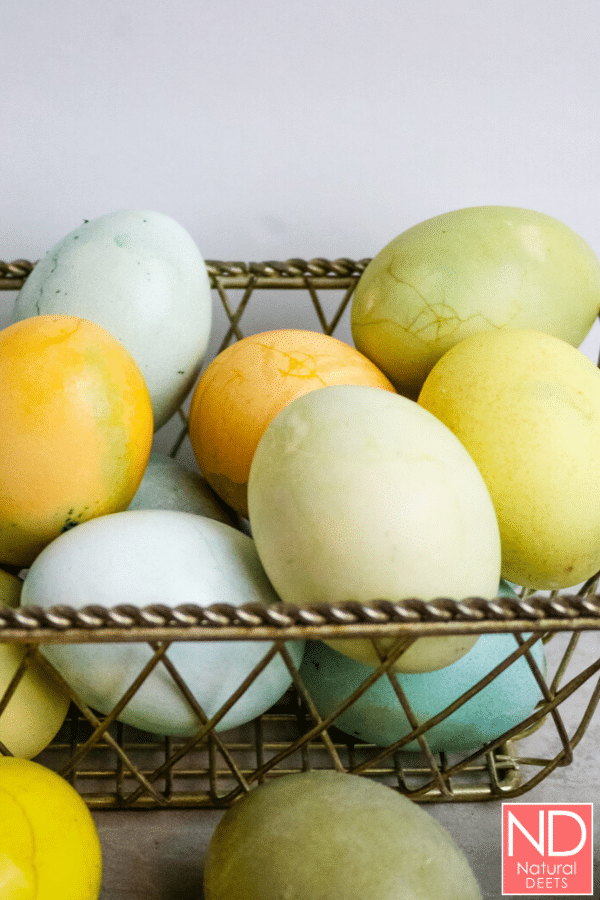 vertical picture with colored eggs in a wire basket