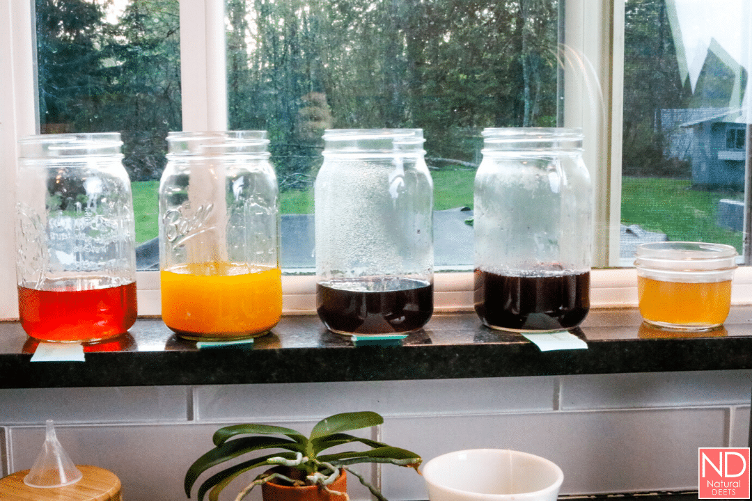 picture of all the different colored egg dyes in mason jars on the window sill
